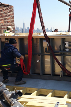Once on the roof, a crew begins to secure the pool in place