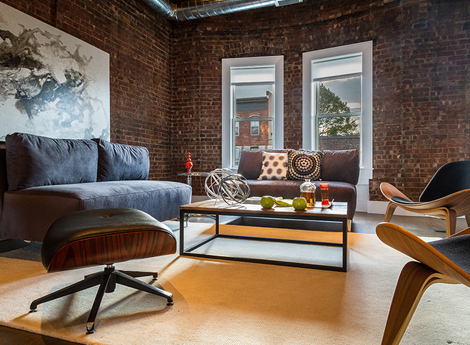 has become a beautiful sitting room with brick walls and soaring ceilings